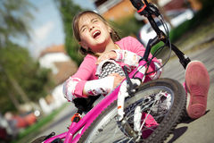 Young girl fell from the bike in a park Stock Image