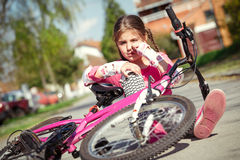 Young girl fell from the bike in a park stock photography