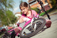 Young girl fell from the bike in a park Royalty Free Stock Photos