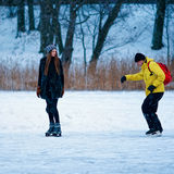 Young girl and fellow ice skating in winter Trakai Stock Photo