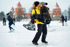 Young girl and fellow kissing at the rink in Trakai. Young girl and fellow kissing at the winter rink covered with snow in Trakai, Lithuania Royalty Free Stock Photos