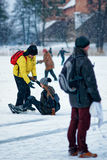 Young girl and fellow at the winter rink in Trakai. Young girl fell down and young fellow learning her to ice skate at the winter rink covered with snow in Royalty Free Stock Photos