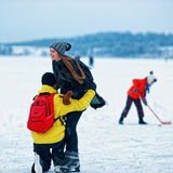 Young girl and fellow at winter rink in Trakai Royalty Free Stock Photo