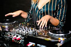 Young girl female shot party dj audio controlling mixing. Turntable High quality Sound mixing controller disc jockey hands of woma. N in night club party, Pro royalty free stock photography