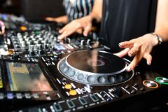 Young girl female shot party dj audio controlling mixing. Turntable High quality Sound mixing controller disc jockey hands of woma. N in night club party, Pro royalty free stock photo