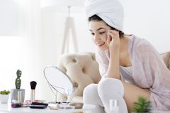 Young female after shower doing make up. Young girl female woman after shower wearing white underwear and white towel sitting on sofa and doing make up / stock photography