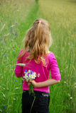 Young girl  on field. Young girl on field with bunch of wild flowers hiding  behind the back Stock Photography