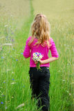 Young girl  on field. Young girl on field with bunch of wild flowers hiding  behind the back Royalty Free Stock Photography