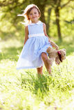 Young Girl In Field Carrying Teddy Bear Stock Images
