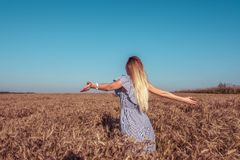 Young girl in field. Summer bright sunny day. Arms outstretched backs. Gentle dress and long hair, tanned skin. The. Young girl in the field. Summer bright sunny stock image