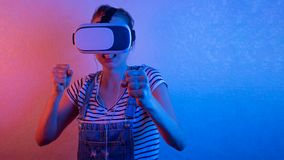 Young girl fights in vr glasses, plays with blue and red light.  royalty free stock photography