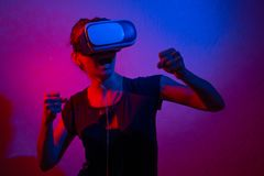 Young girl fights in vr glasses, plays with blue and red light.  stock images