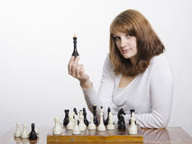 A young girl with a figure of the Queen, at the chess Board Royalty Free Stock Image