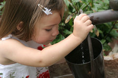 Young girl filling bucket. From tap Royalty Free Stock Images