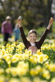 Young girl finding Easter eggs in field of daffodils Stock Photography