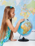 Young girl finding places on a globe Stock Images