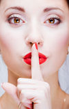 Young girl with finger by lips Royalty Free Stock Image