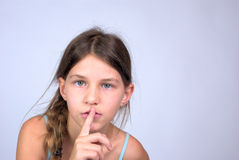 Young girl with finger on lips shushing Stock Photo