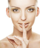 Young girl with  finger over her mouth Royalty Free Stock Images