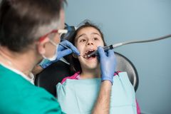 Young girl on the first dental visit. Senior pediatric dentist treating patient girl teeth at the dental office. Medicine, stomatology and health care concept stock photo
