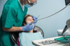 Young girl on the first dental visit. Senior pediatric dentist treating patient girl teeth at the dental office. Medicine, stomatology and health care concept royalty free stock photography