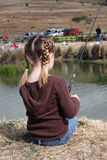 Young Girl Fishing. Young girl sitting beside a pond holding a fishing pole Stock Photo