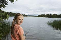 Young Girl Fishing At Lake Stock Photo