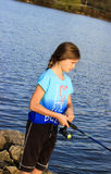 Young Girl Fishing. A young girl fishing at the lake royalty free stock photo