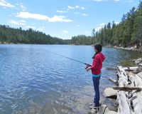 A young girl fishing in a mountain lake Stock Image