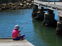young Girl fishing on pier  Stock Photography