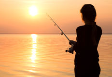 Young girl fishing at sunset near the sea Royalty Free Stock Image