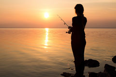 Young girl fishing at sunset near the sea Stock Photos