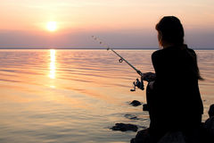 Young girl fishing at sunset near the sea Royalty Free Stock Photography