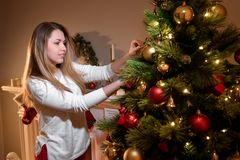 Young girl fixing new year tree decorations in room royalty free stock photos