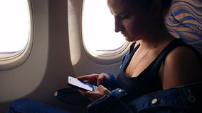 A young girl flies in an airplane and looks at photos in the smartphone. stock footage