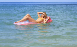 Young girl floating on a mattress in the sea Stock Image