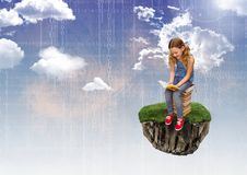 Young Girl on floating rock platform  in sky reading books with numbers interface Royalty Free Stock Photography