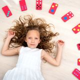 Young girl on floor with domino pieces Royalty Free Stock Photo