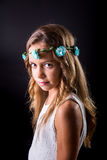 Young girl with flower tiara and sober look on black background. Young girl with long hair and flower tiara posing with a sober look on a black background Royalty Free Stock Images