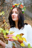 Young girl with flower wreath among branches of autumn in the park Royalty Free Stock Images