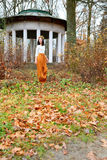 Young girl with flower wreath near the gazebo in autumn park Stock Image
