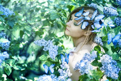 Young girl with flowers and tropical butterfly. Sitting on her Royalty Free Stock Image