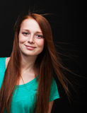 Young girl with flowing red hair on a black background Stock Photos