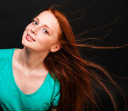 Young girl with flowing red hair on a black background Royalty Free Stock Image