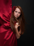 Young girl with flowing red hair on a black background Royalty Free Stock Photo