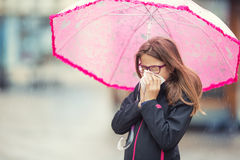 Young girl with flu blowing her nose with a tissue paper under spring rain. Pre-teen girl sneezing and wearing warm clothes against cold weather. Depression Royalty Free Stock Image