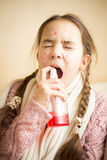 Young girl with flu using throat spray Stock Image