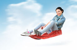 Young girl fly on a sled in the snow Royalty Free Stock Photography