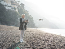 Young girl flying drone over italian coast. Stock Image