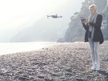 Young girl flying drone over italian coast. stock image